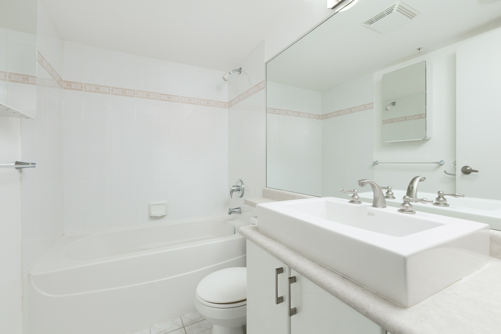 All white bathroom with sink, mirror, toilet and bath in Vancouver rental condo property in River District neighbourhood