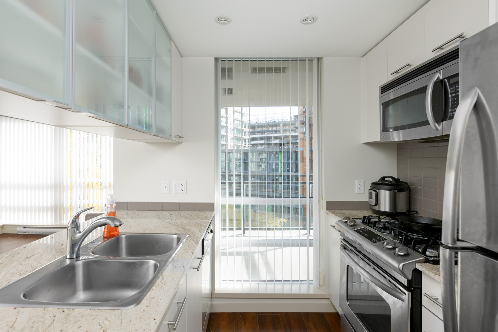 condo kitchen with bright sunlight coming in through tall wall to ceiling window
