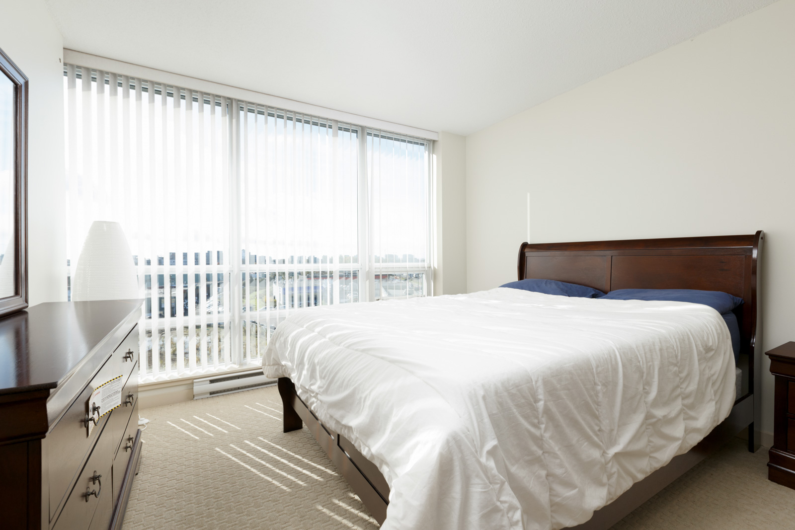 condo bedroom in richmond bc with bed with white sheets and floor to ceiling windows