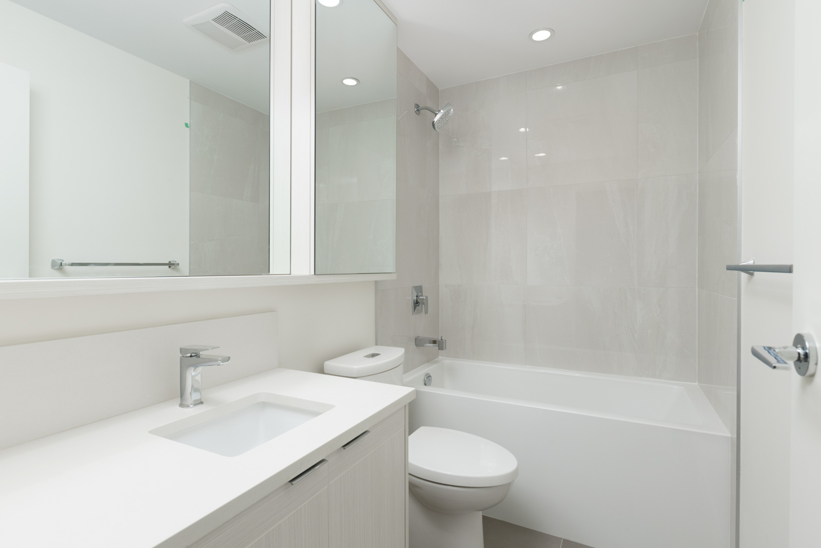 bathroom with mirror and white countertop and toilet and bathtub