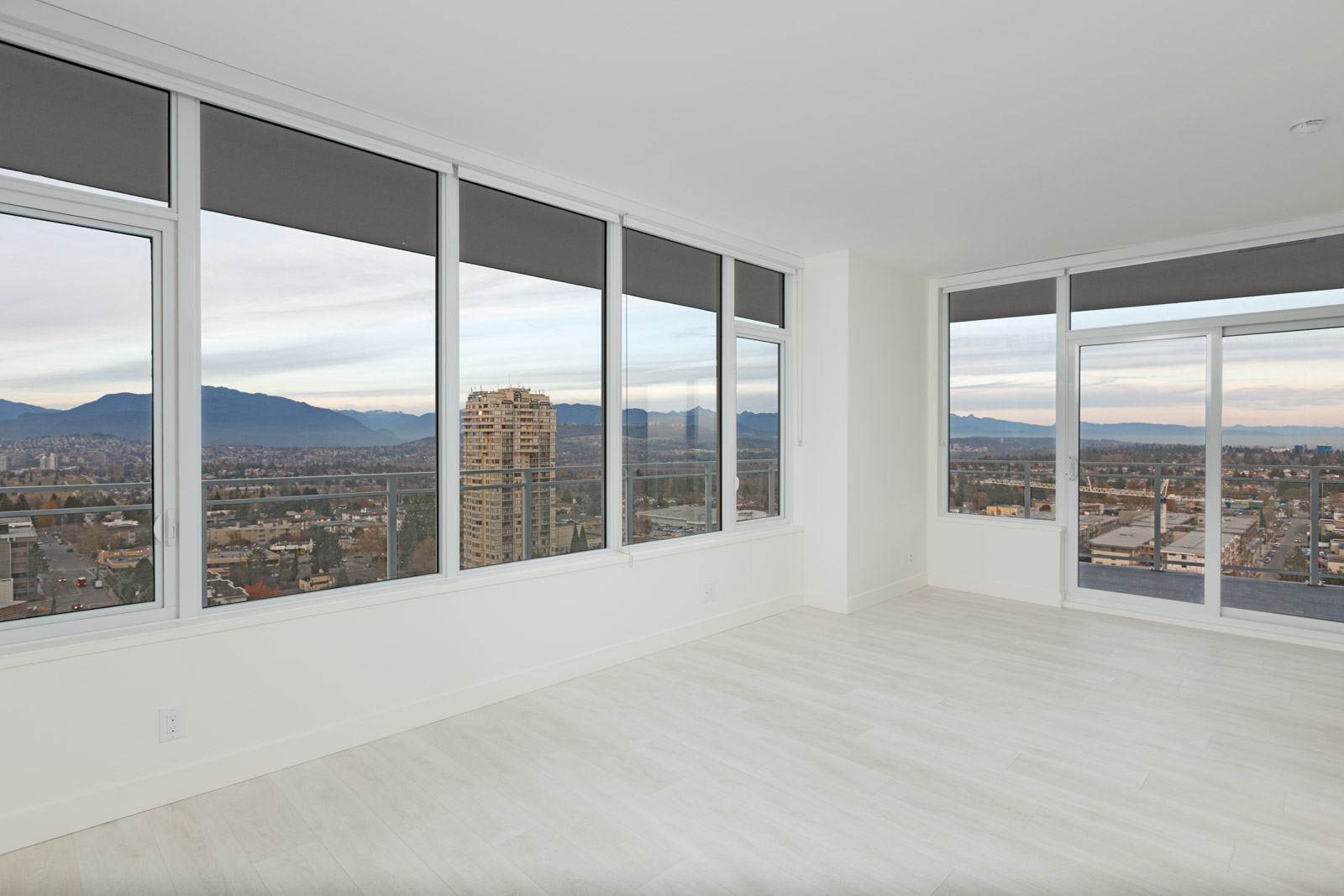 living room with white walls and large windows with mountain views from burnaby metrotown condo