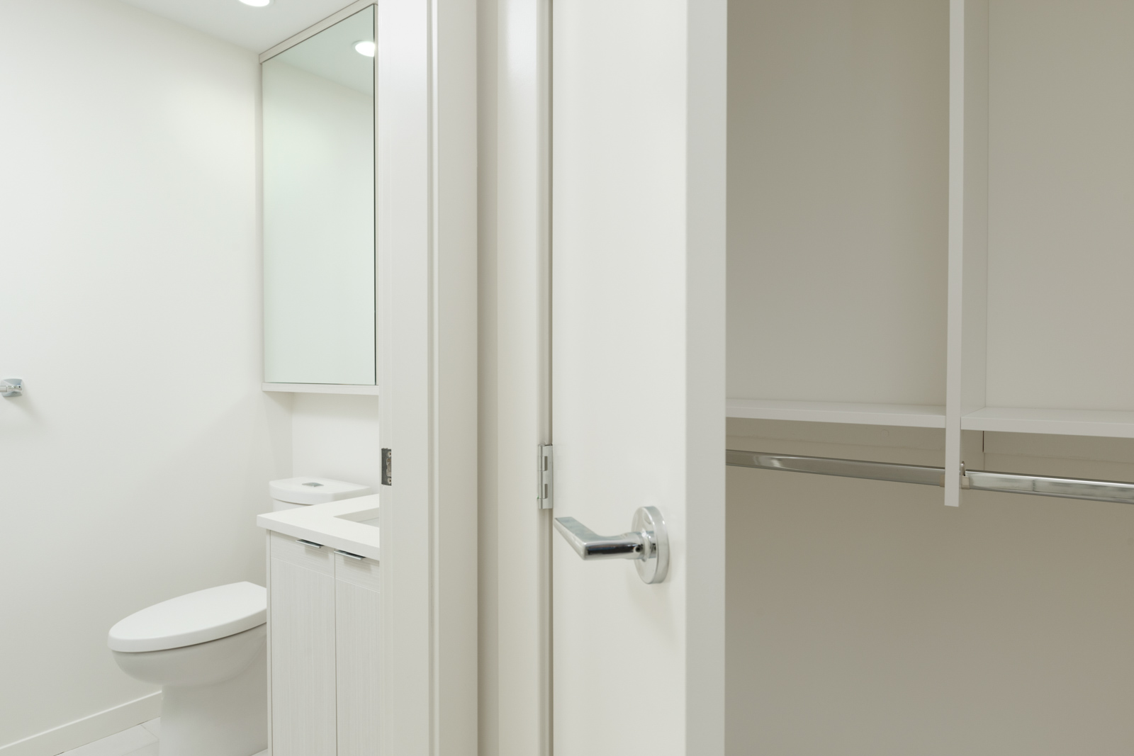 closets and bathroom with white doors and silver chrome handles in burnaby condo