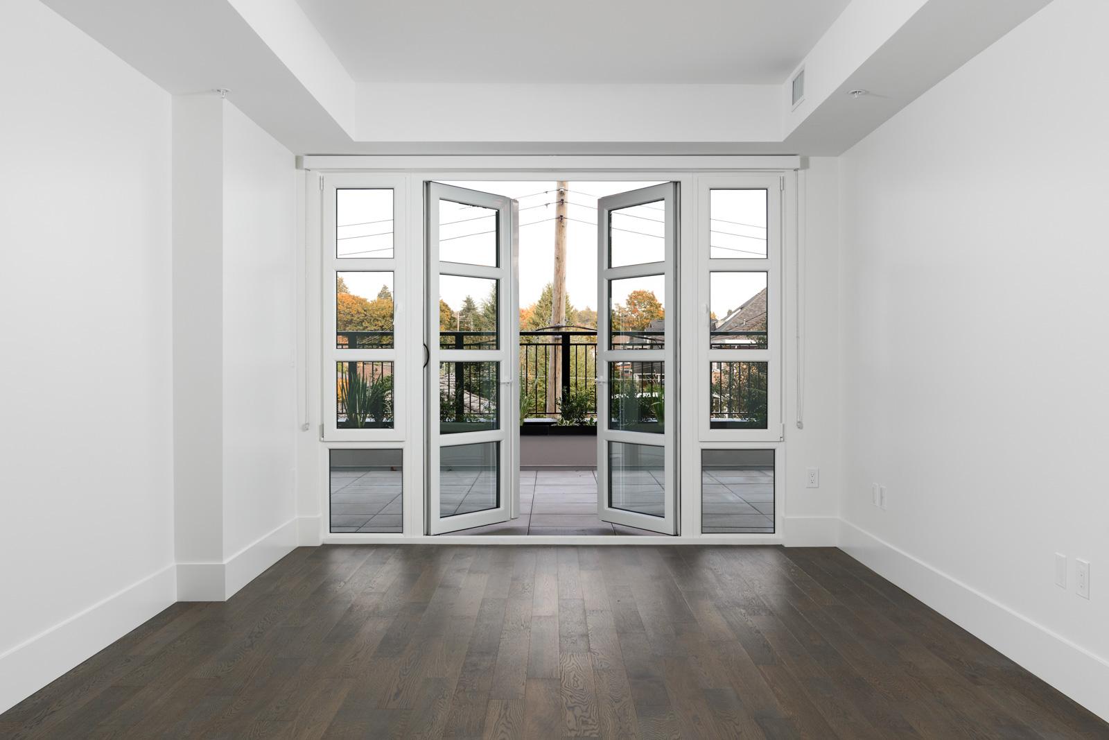 Living room of condo with dark brown hardwood floors with open window doors onto patio