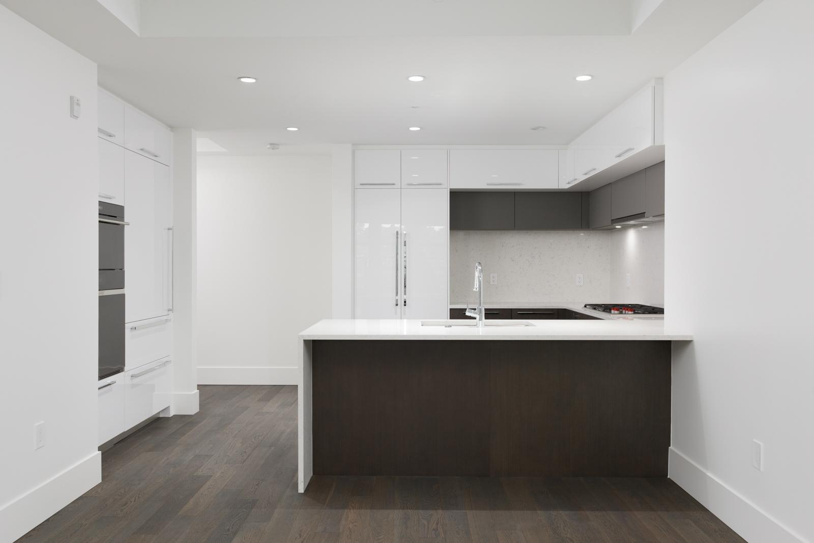 Condo kitchen with dark hardwood floors and quartz countertops in rental property in The Kirkland