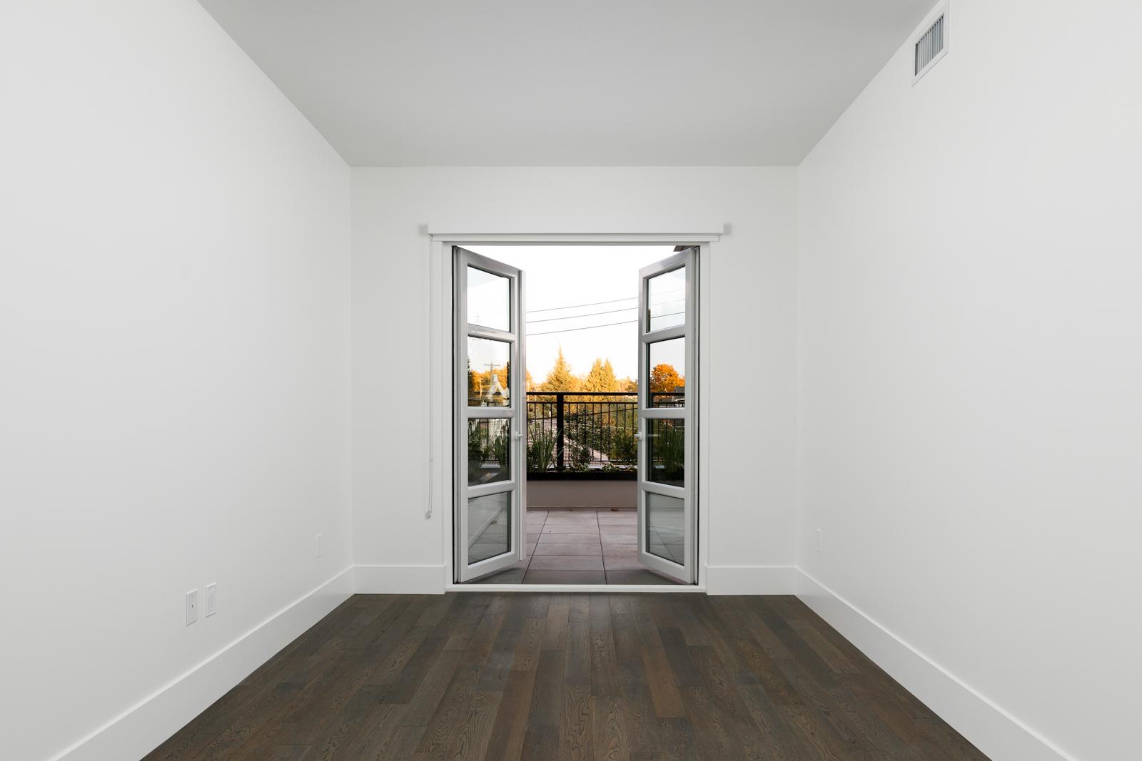 Bedroom with open windowed doors onto patio in rental property in The Kirkland building in Kerrisdale Vancouver