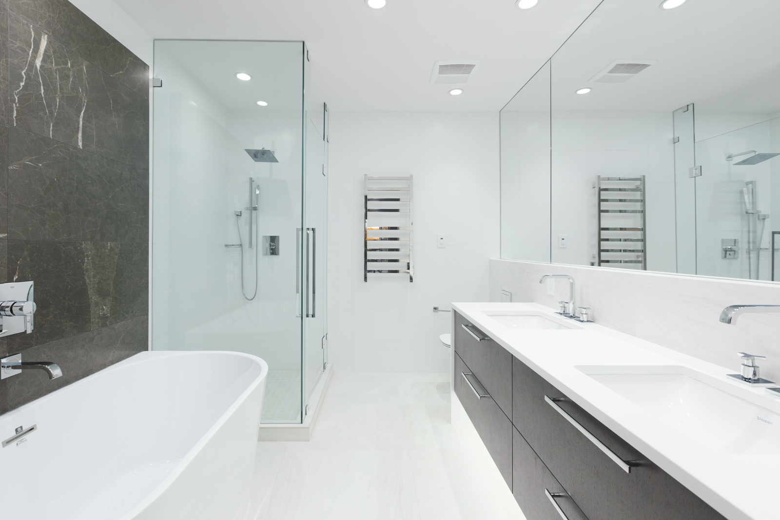 Bathroom with white floors and counters and glass door shower in rental property in The Kirkland building in Kerrisdale Vancouver