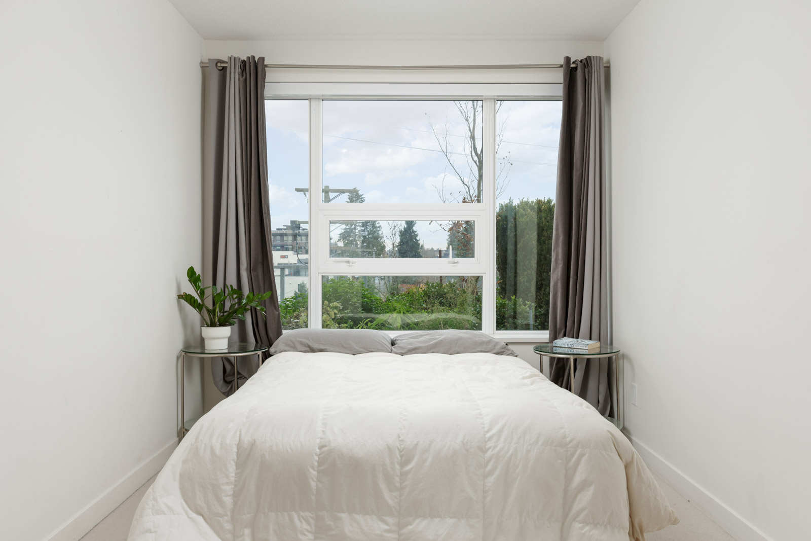 bed made with white sheets underneath window with open drapes to bright skies outside