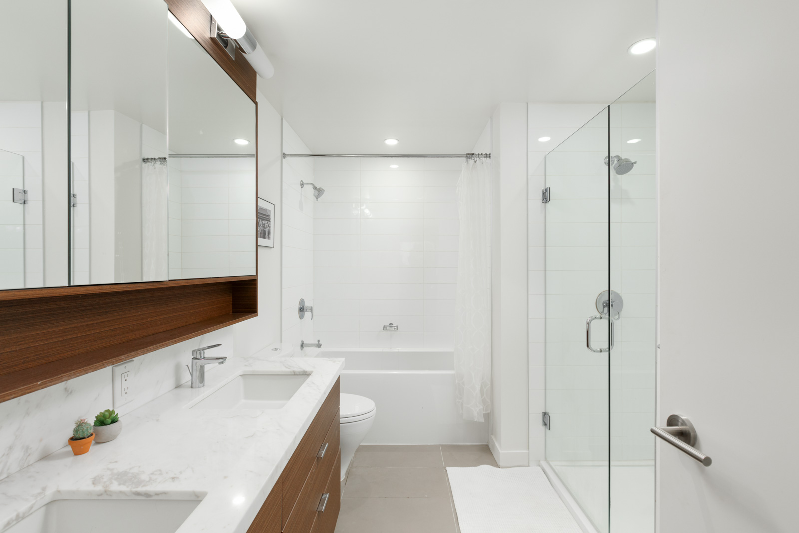 white bathroom with countertops, mirror, glass enclosed shower