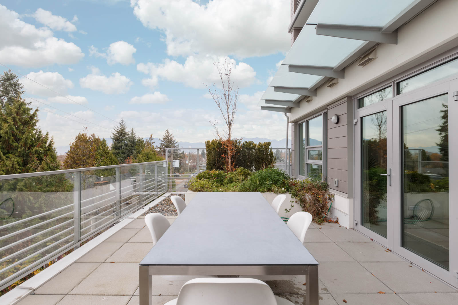 rectangular patio table with four white chairs on large condo patio with bright sky and clouds