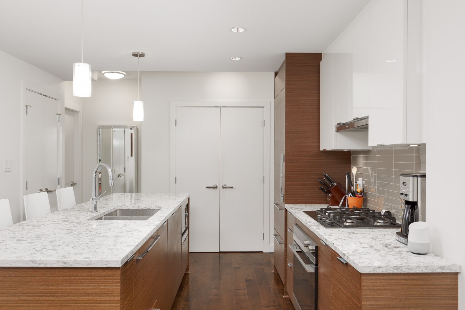 condo kitchen with white countertops and wood cabinets and white doors and walls in background