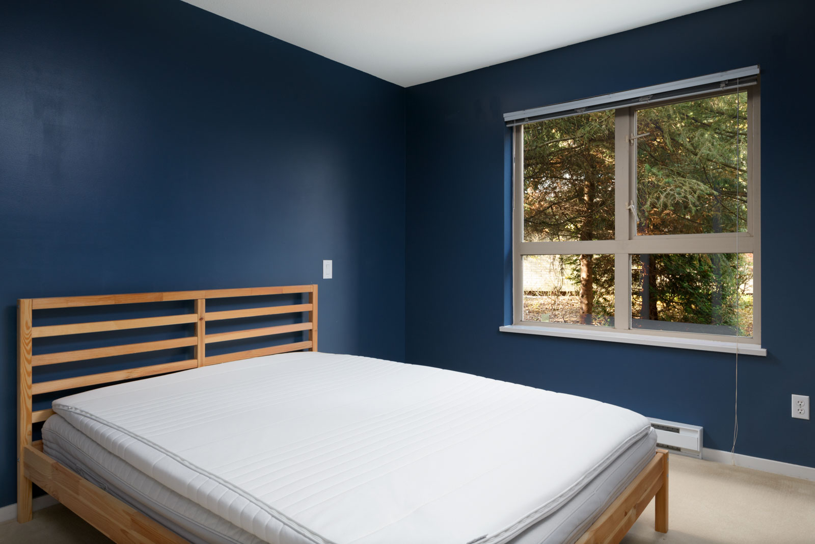 bedroom with white bed mattress and blue walls with one window