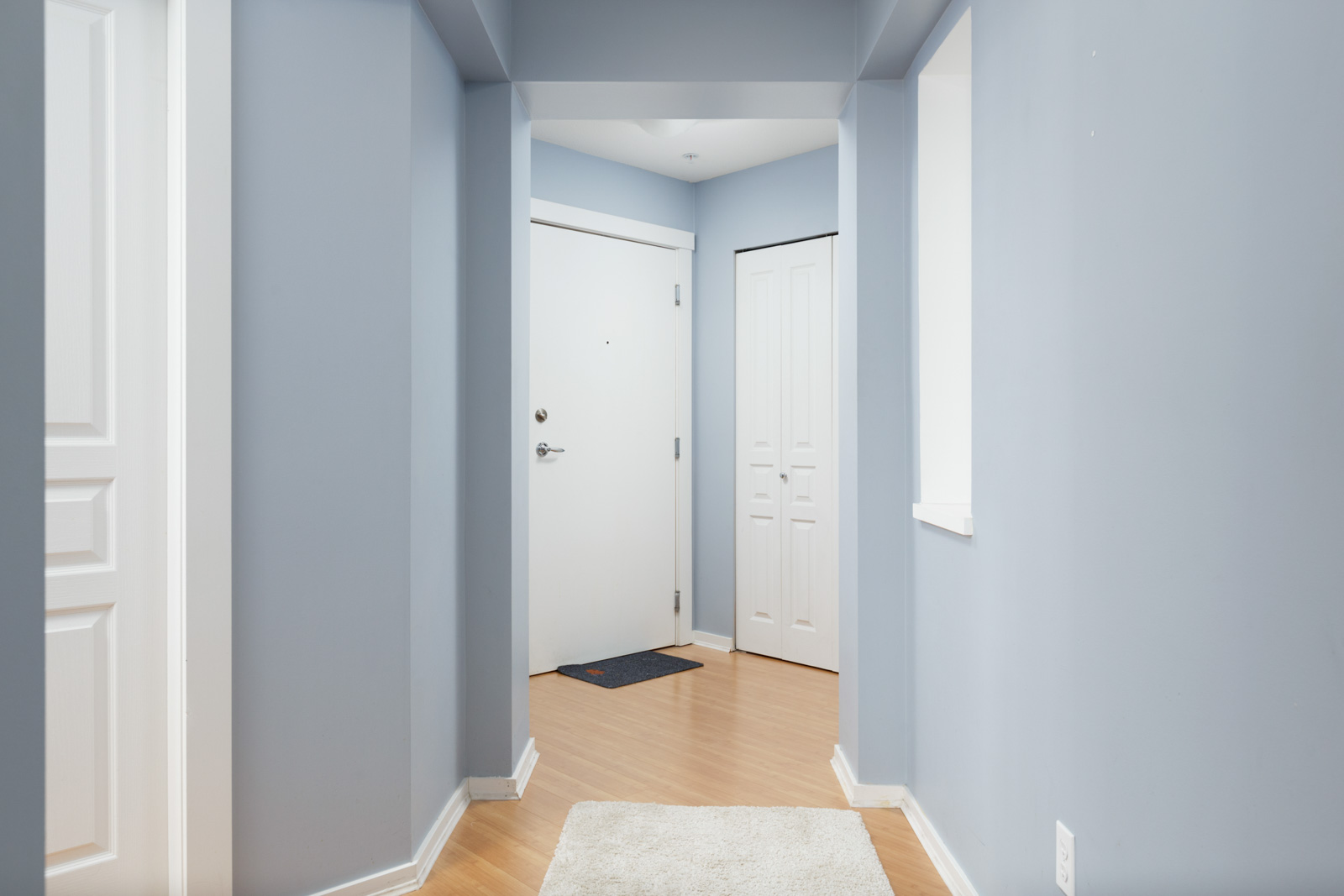 hallway with door and blue walls in burnaby condo for rent