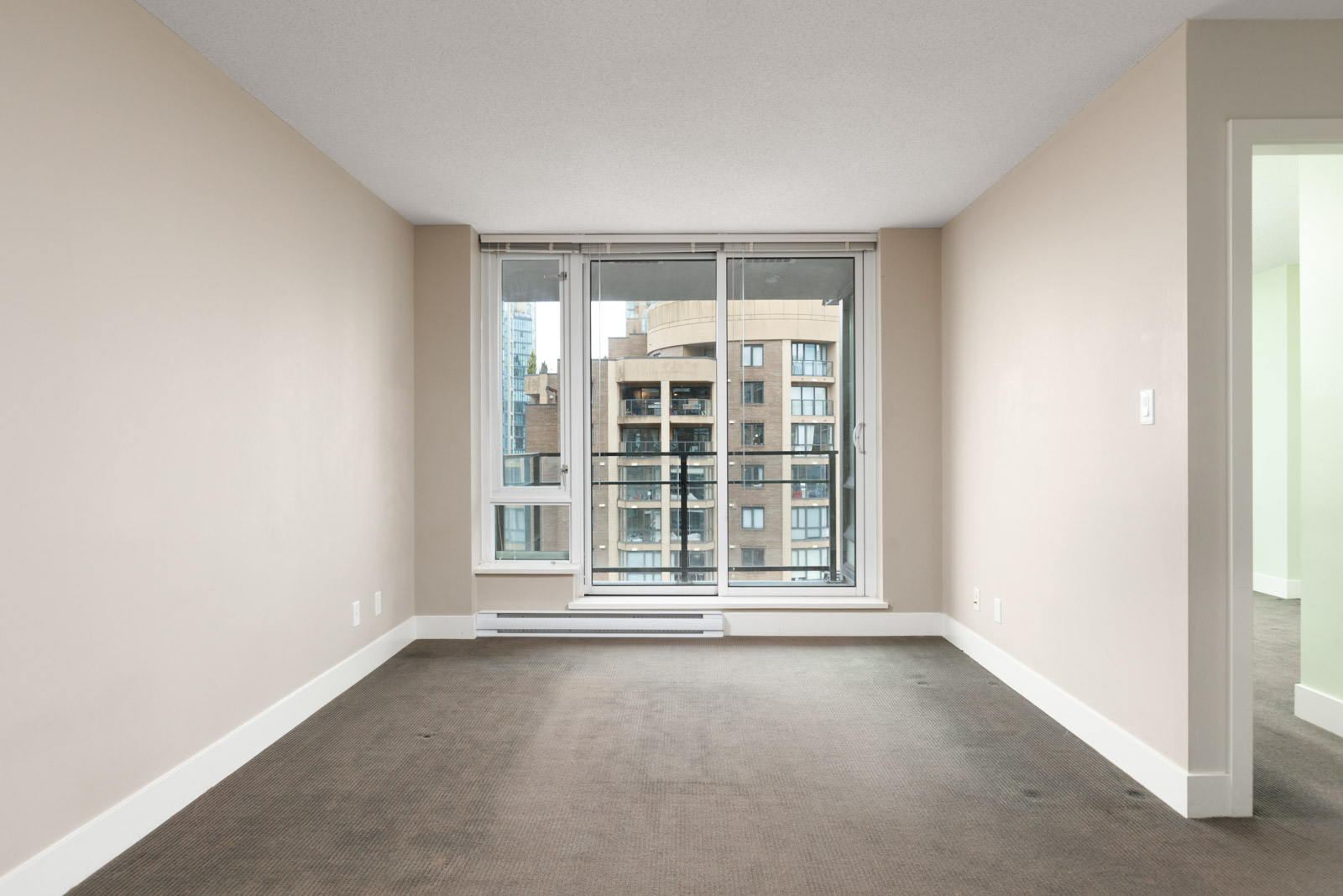 empty condo living room with hardwood floors looking out floor to ceiling windows to next condo building