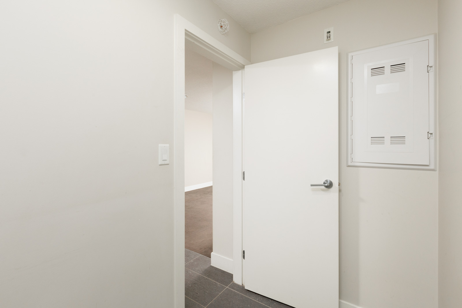 open white door from bedroom in yaletown vancouver condo with hardwood floors