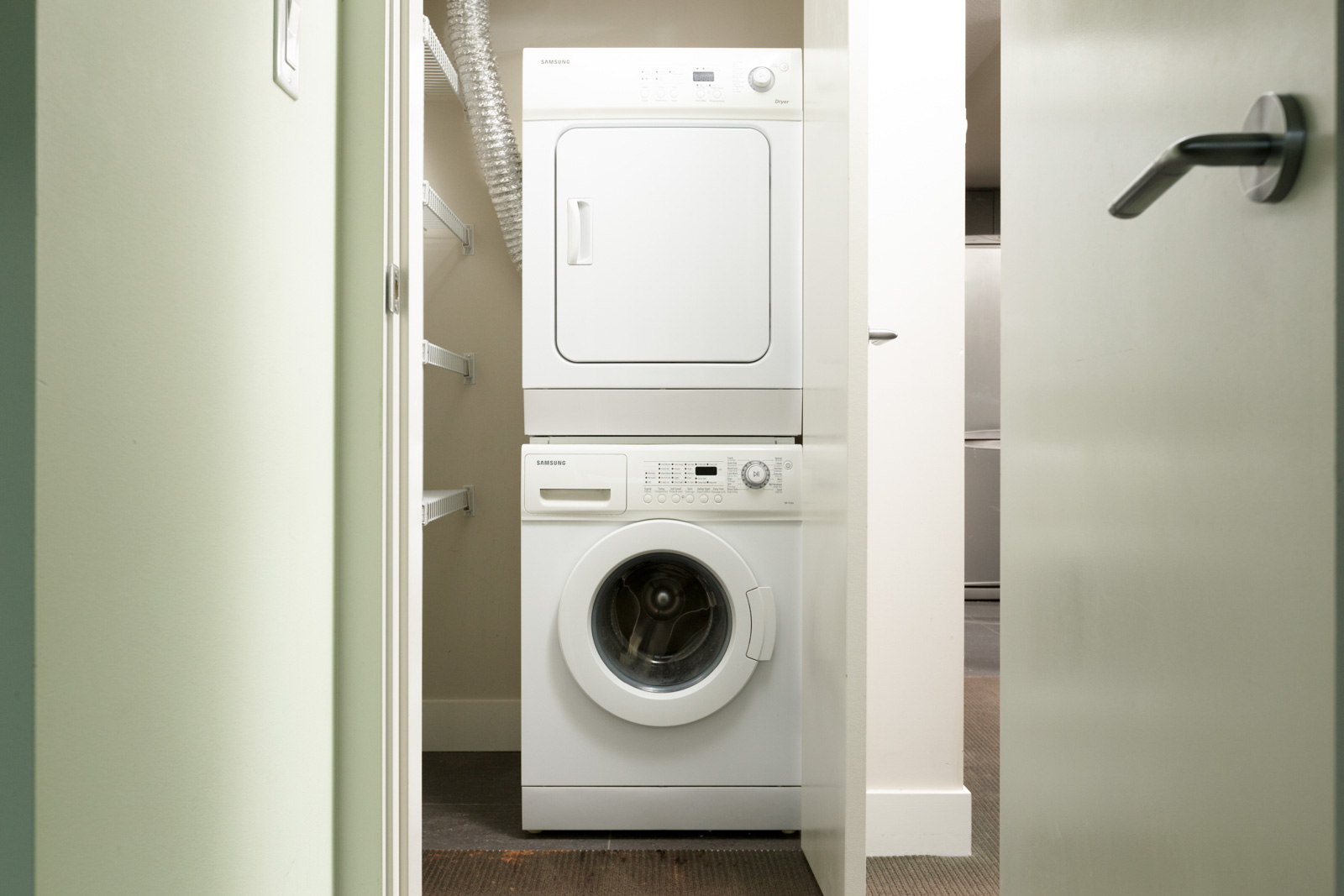 stacked white washer dryer in condo laundry closet