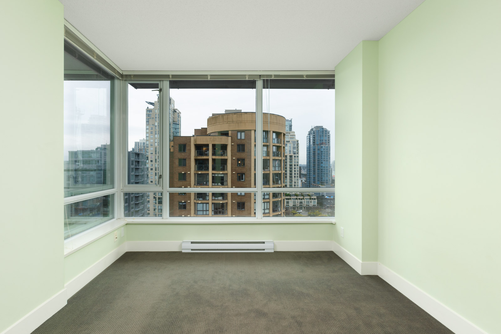condo room with hardwood floors looking out wide windows to buildings across the street