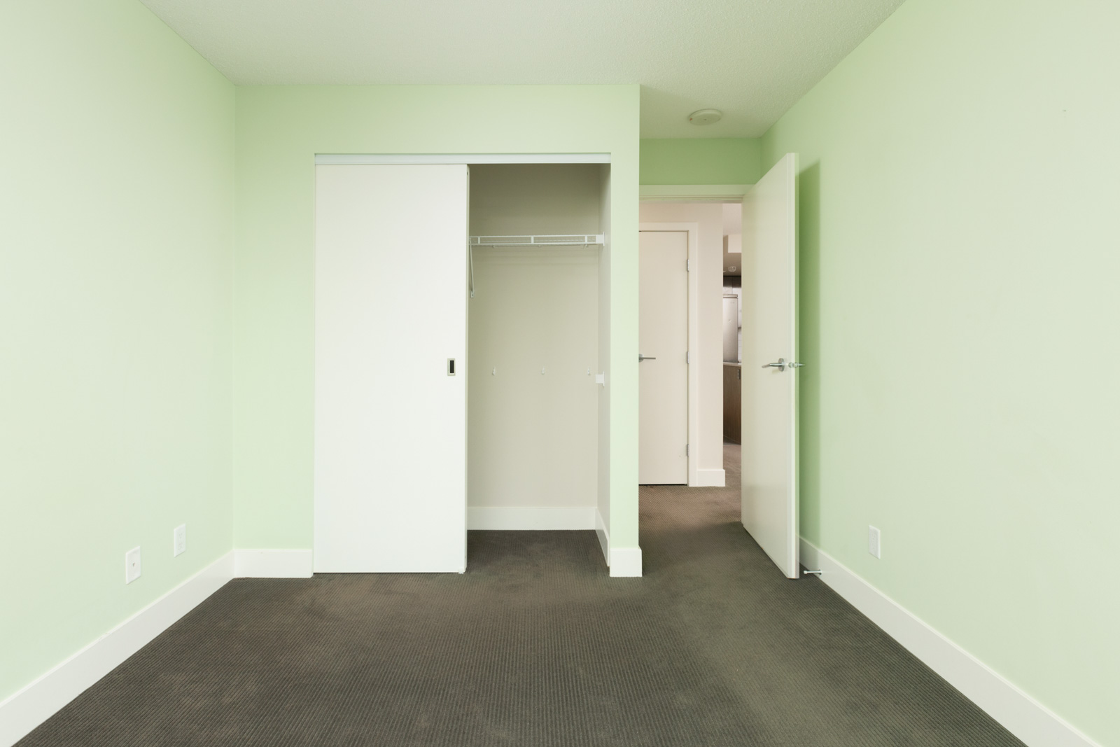 condo bedroom with hardwood floors and closet on left and open door on the right
