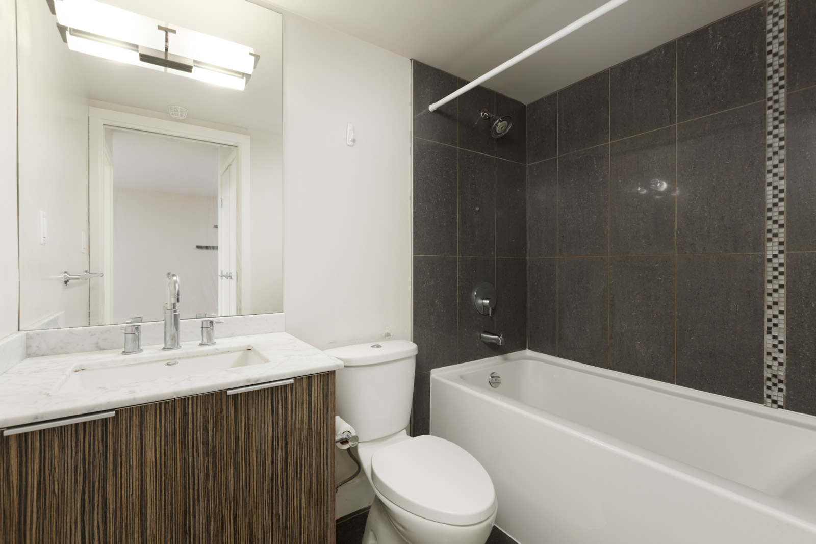 condo bathroom with white bathtub on right and vanity on left and toilet in middle