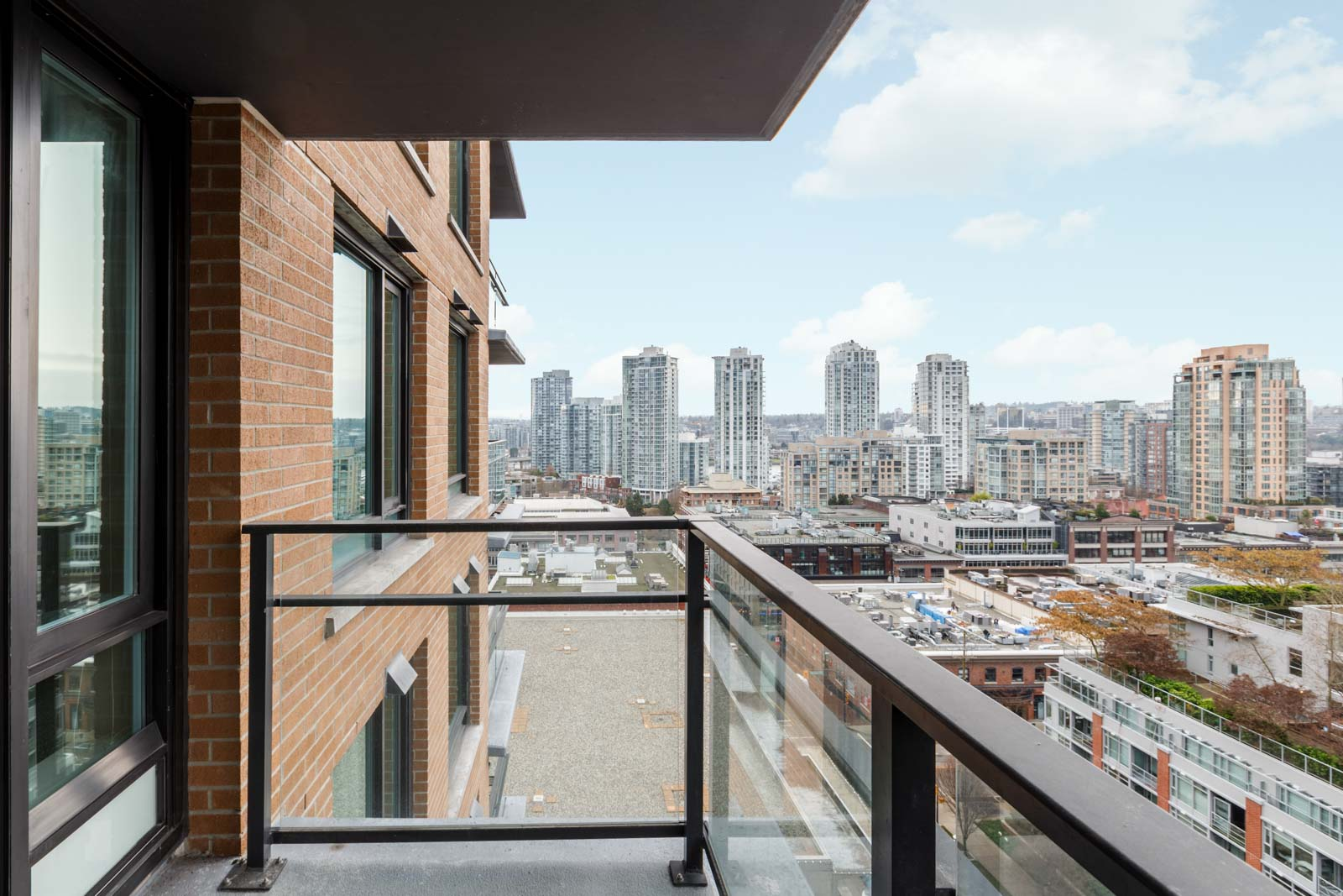 condo balcony with side of building on left and buildings and cloudy bright skies in the background
