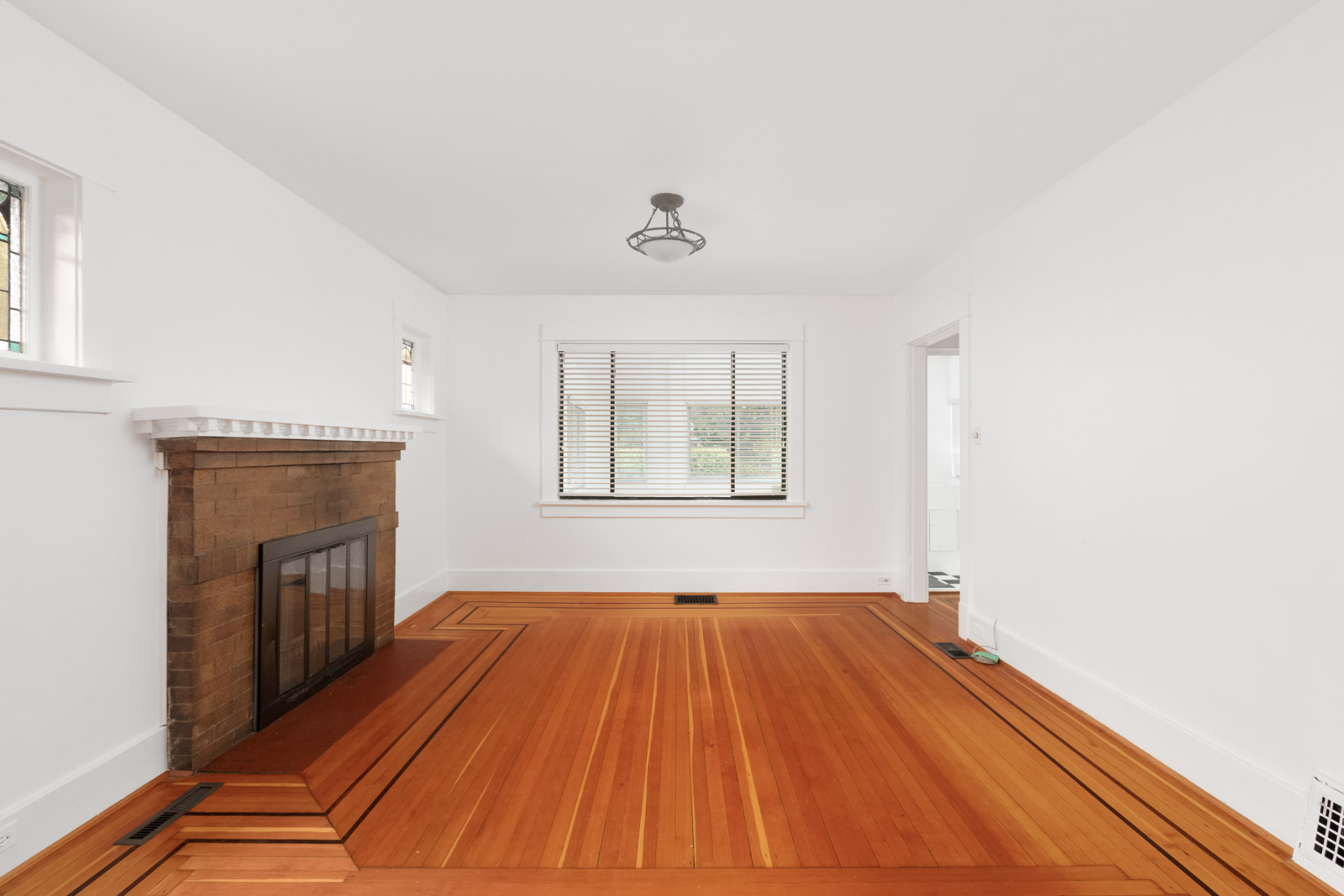 Living room in Kerrisdale Vancouver house with hardwood floor and fireplace on the left