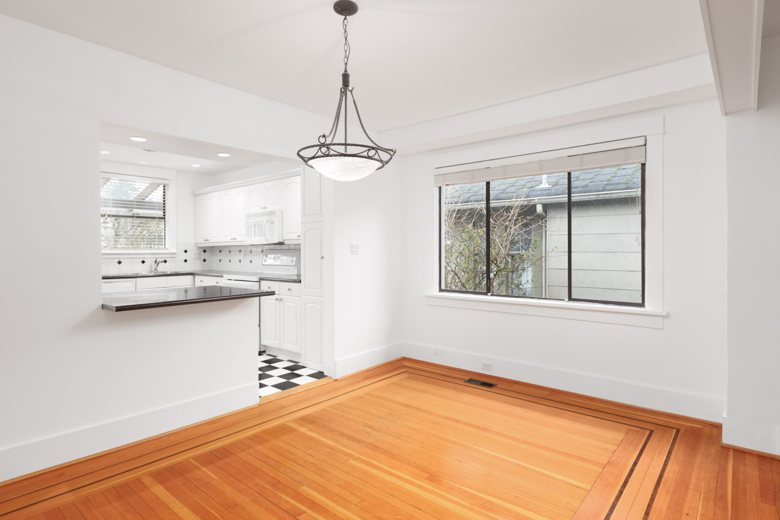 Open transition from kitchen to living area with sleek hardwood flooring and natural light