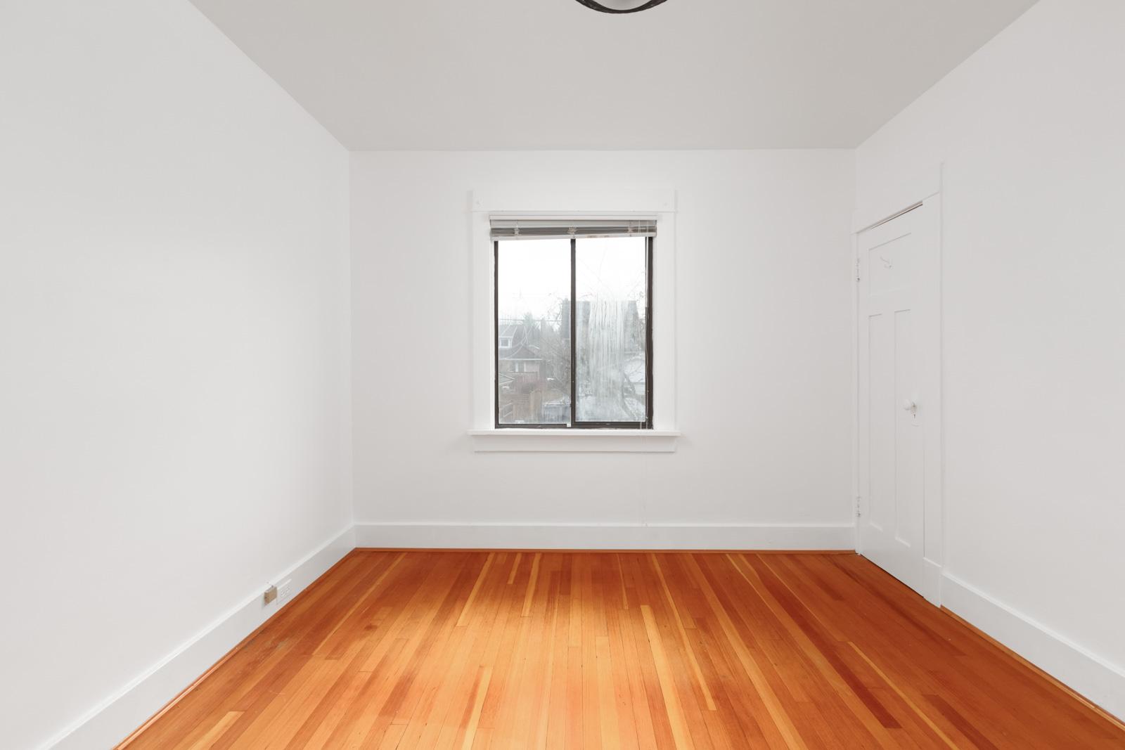Empty bedroom with hardwood floor and plain window in centre of photo