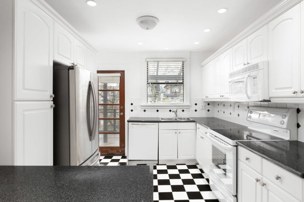 Renovated kitchen with quartz countertops and tile flooring