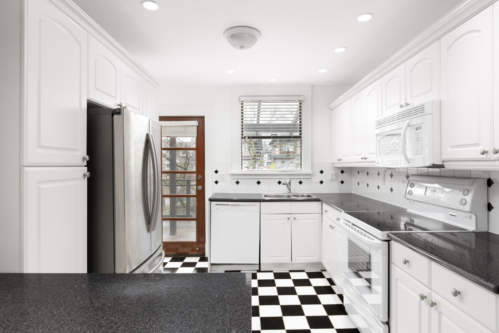 Kitchen with white cabinets and black and white checkered tile floors in Kerrisdale rental house