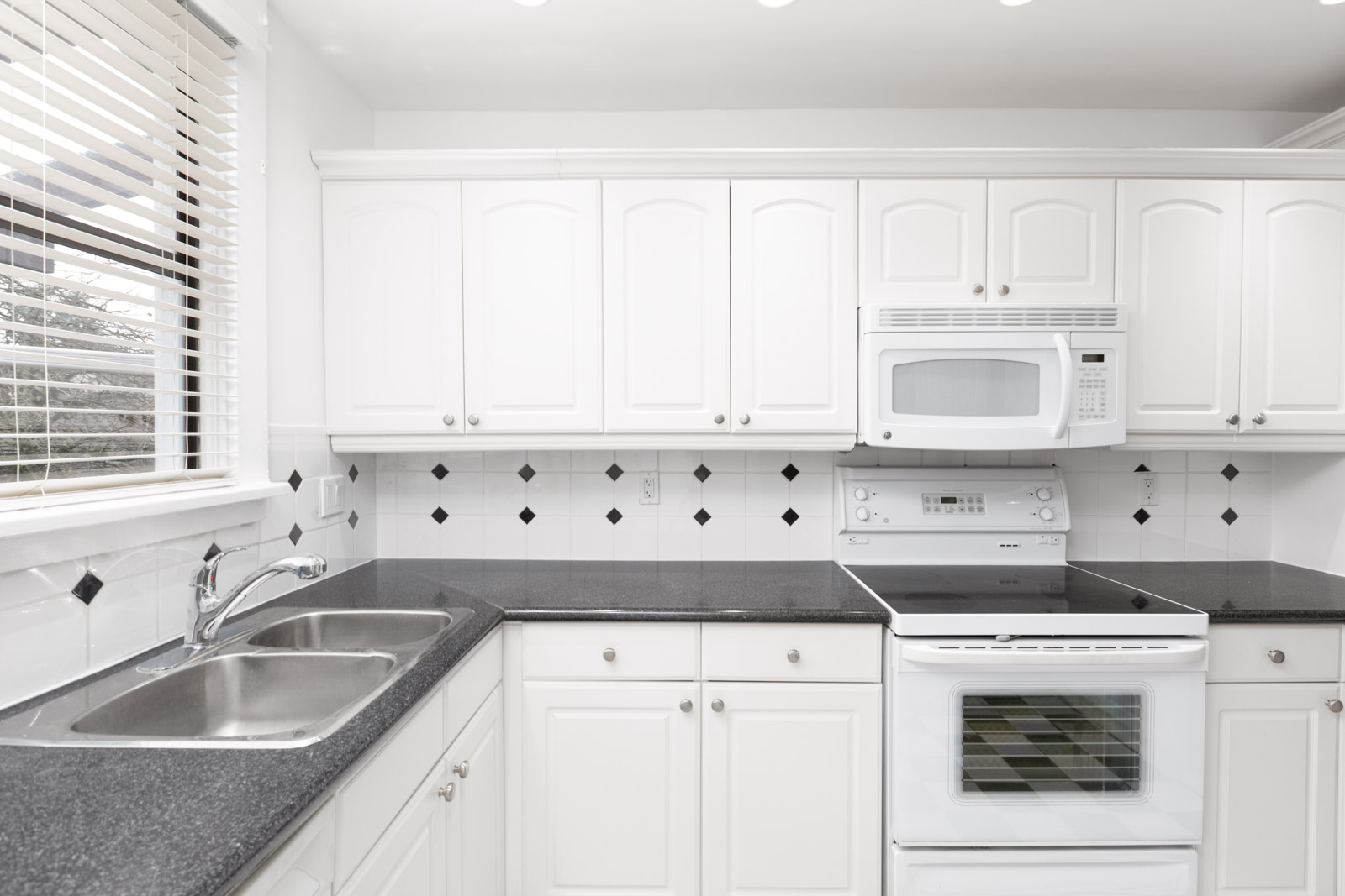 Kitchen with white cabinets with white oven and dark stovetop on left along with over the top white microwave