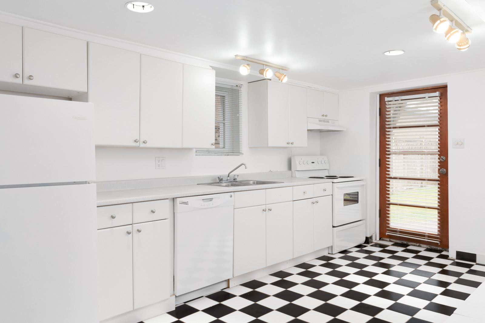 kitchen with checkered black and white floor tiles and white cabinets with door to outside on right