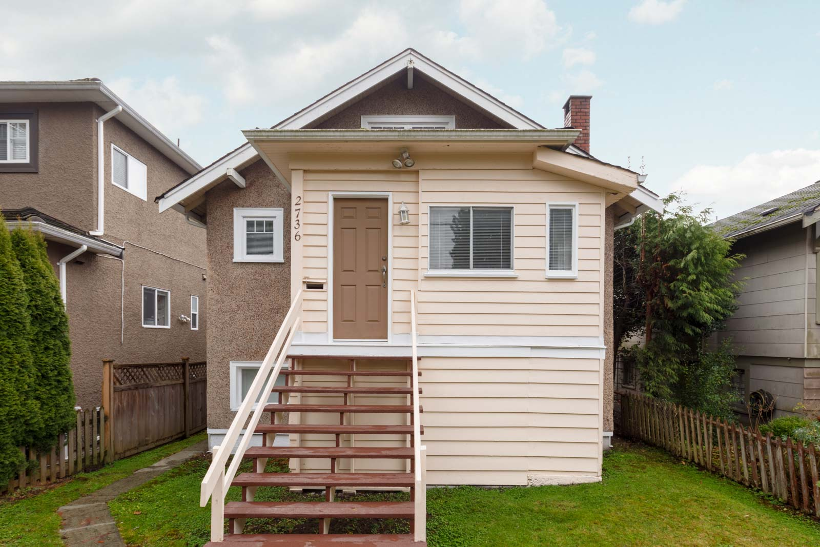 back of kerrisdale vancouver house with yellow siding and for rent and managed by birds nest properties