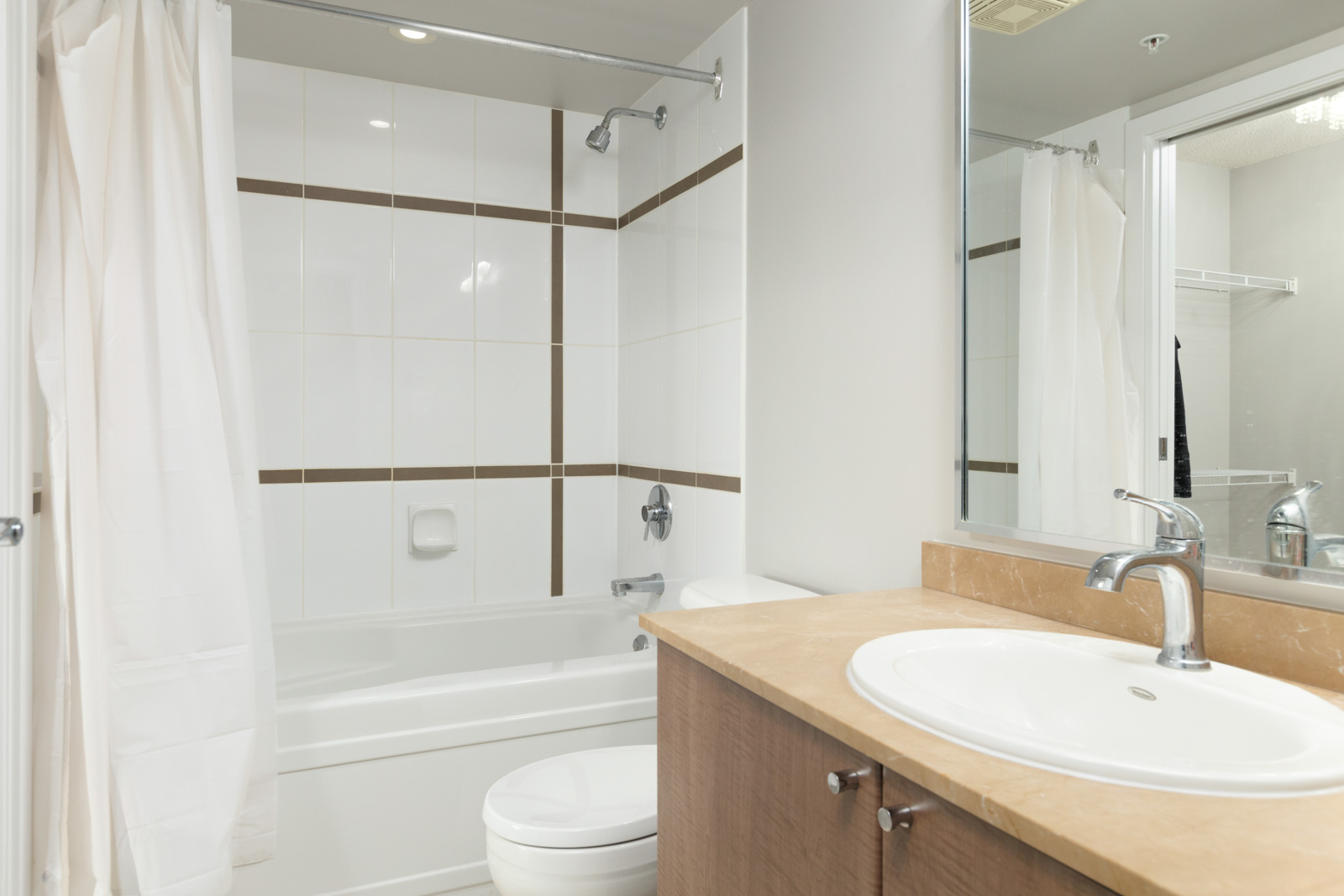 A bathroom with white tiling, white walls and large mirrors