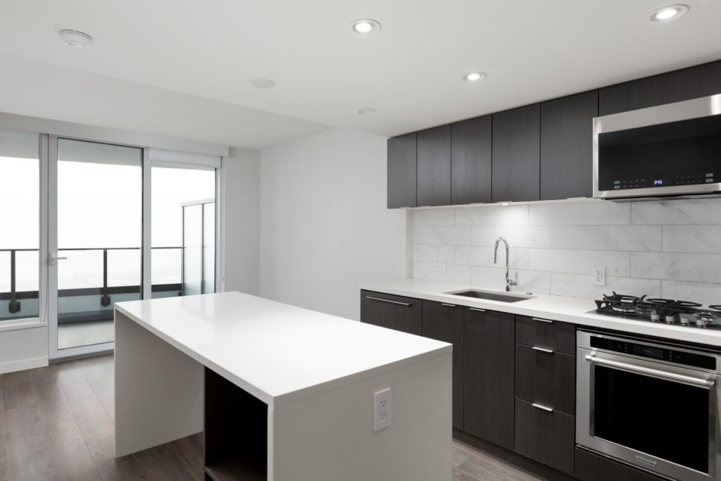 Cambie and marine condo living room with white kitchen island and kitchen and living room windowe
