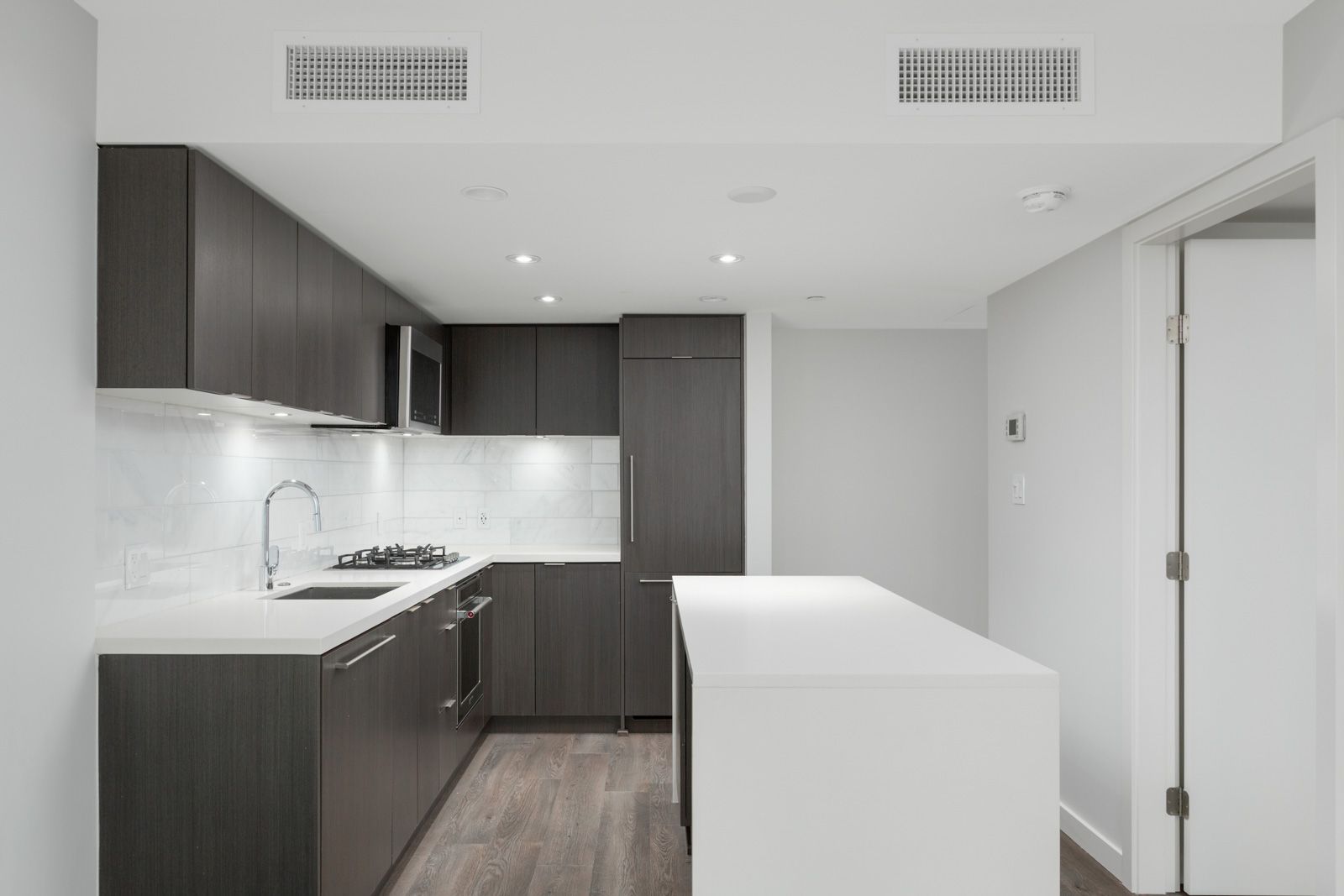 Kitchen with white island counter in rental condo managed by birds nest properties