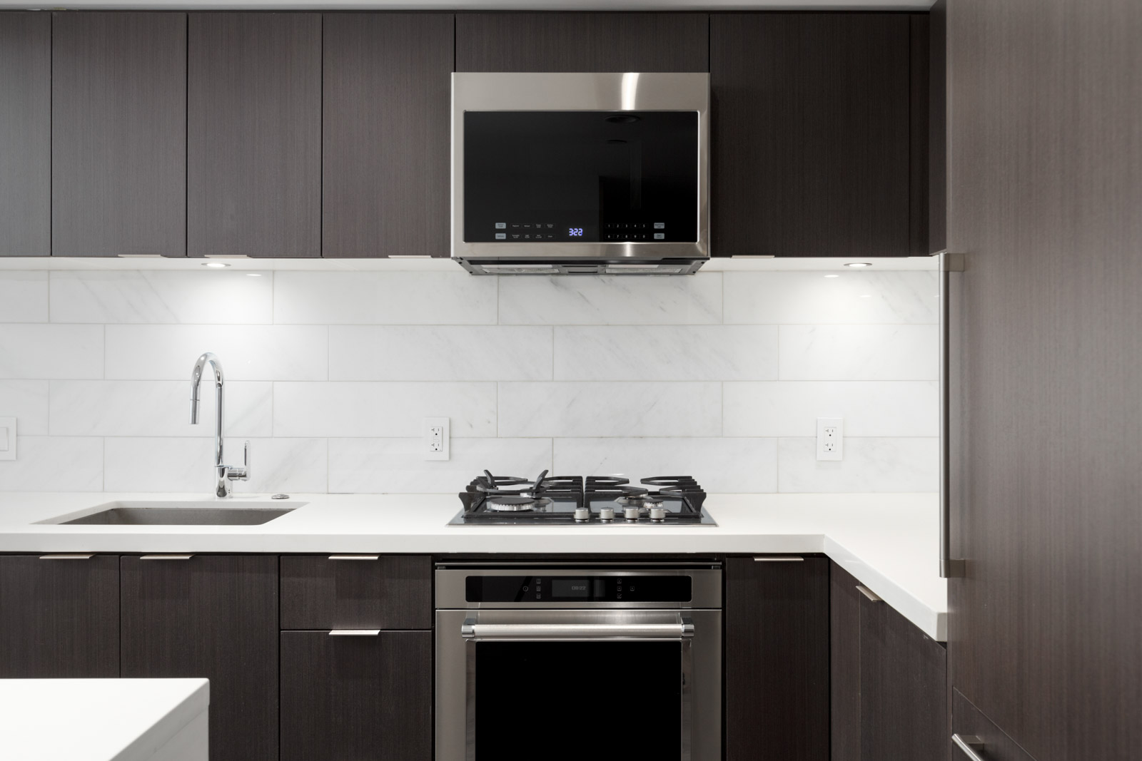 Kitchen with faucet over the top microwave and gas stove range in rental condo managed by birds nest properties