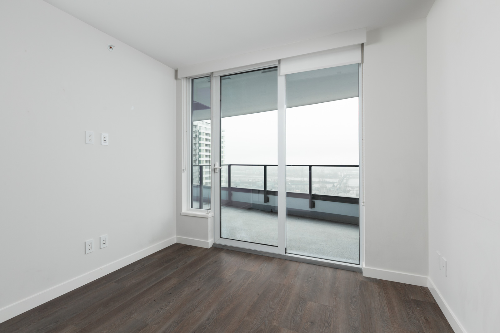 sliding window doors to balcony in rental condo with dark hardwood floors in cambie and marine hub of vancouver