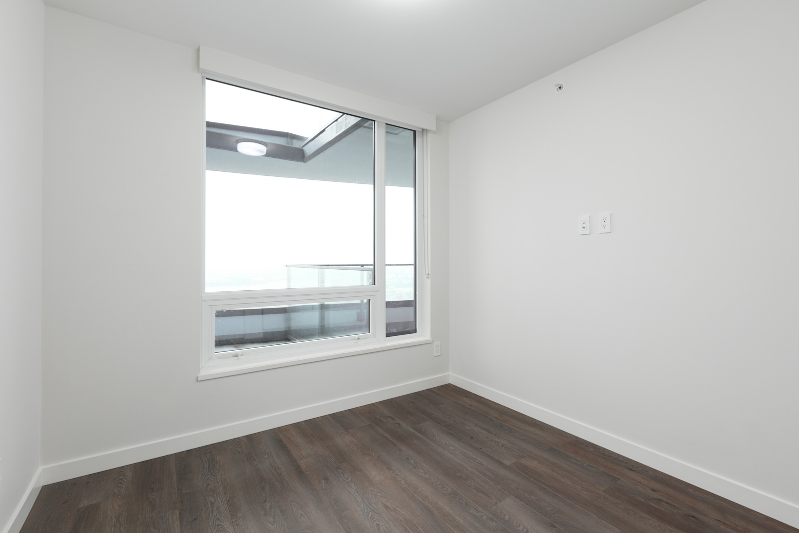 window from bedroom of rental condo with dark hardwood floors and white walls
