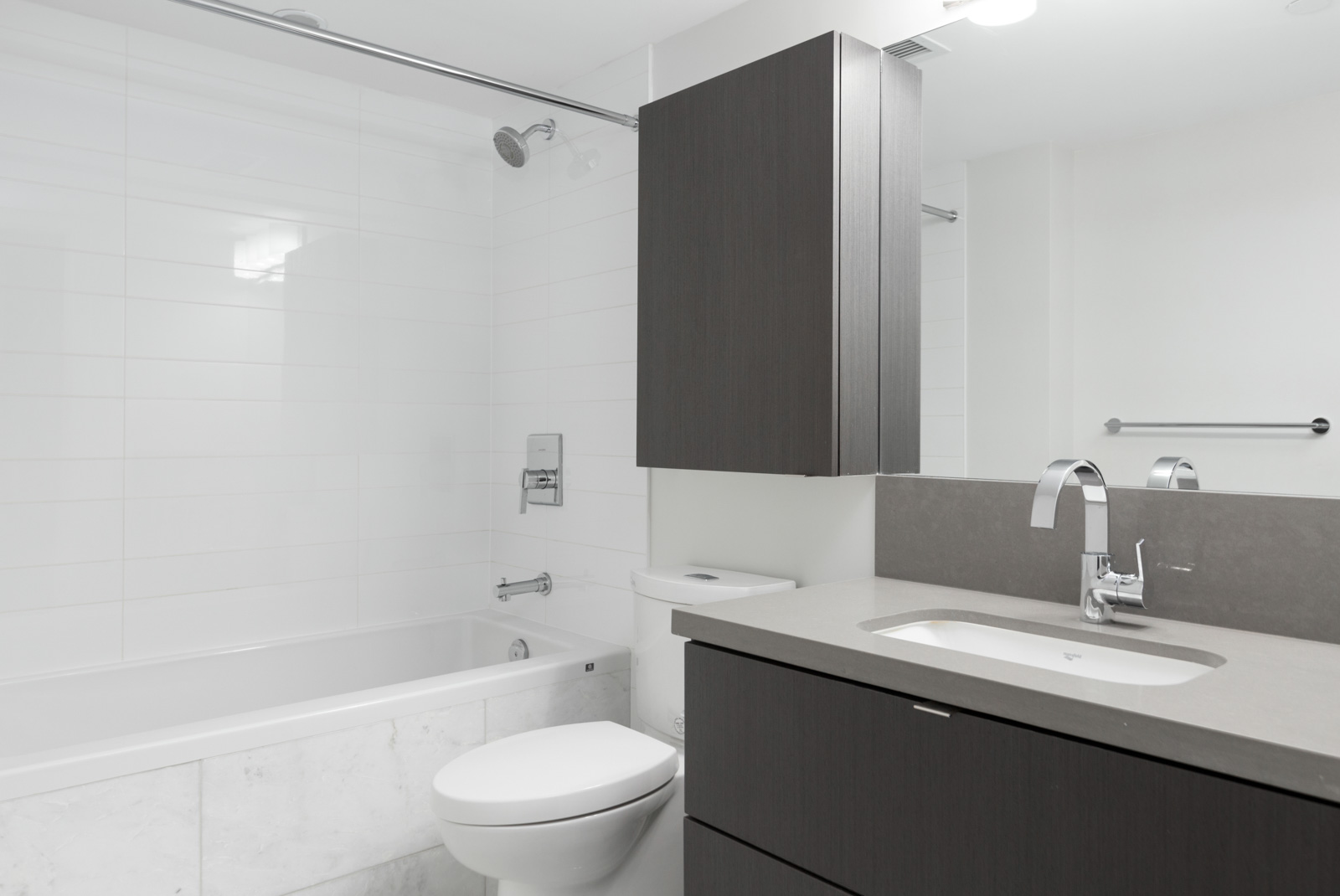 bathroom with toilet bath and vanity with mirror in rental condo in cambie and marine hub of vancouver