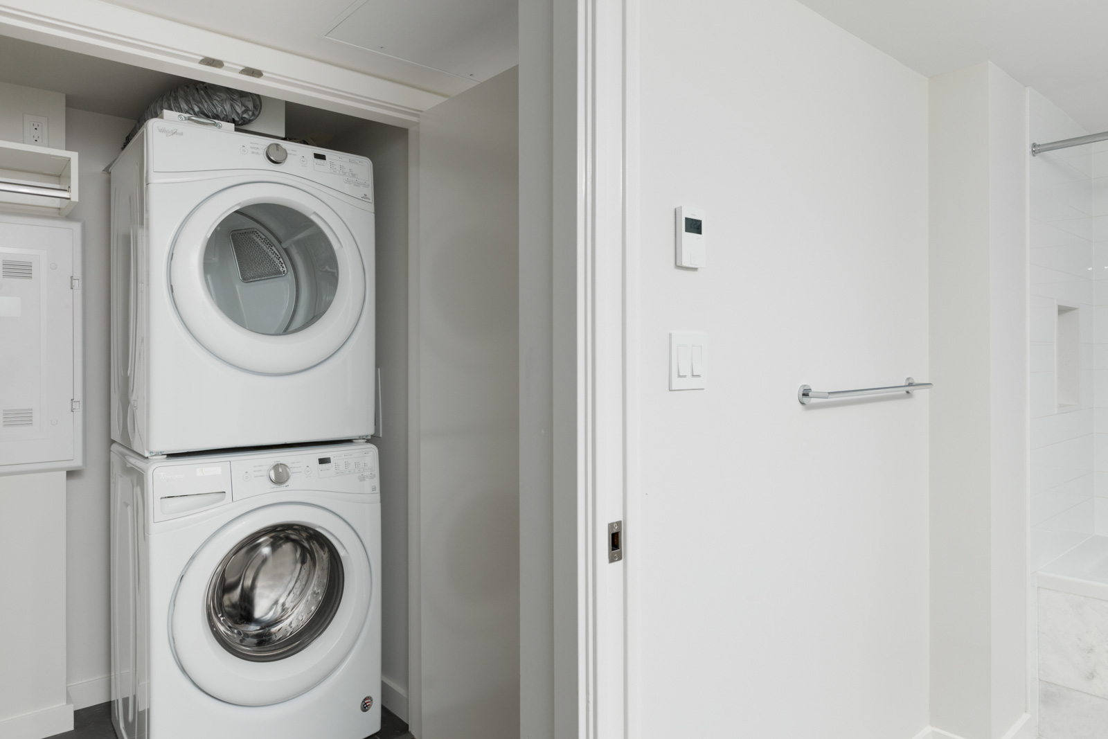 white stacked washer dryer in laundry closet and white walls in rental condo in cambie and marine hub of vancouver