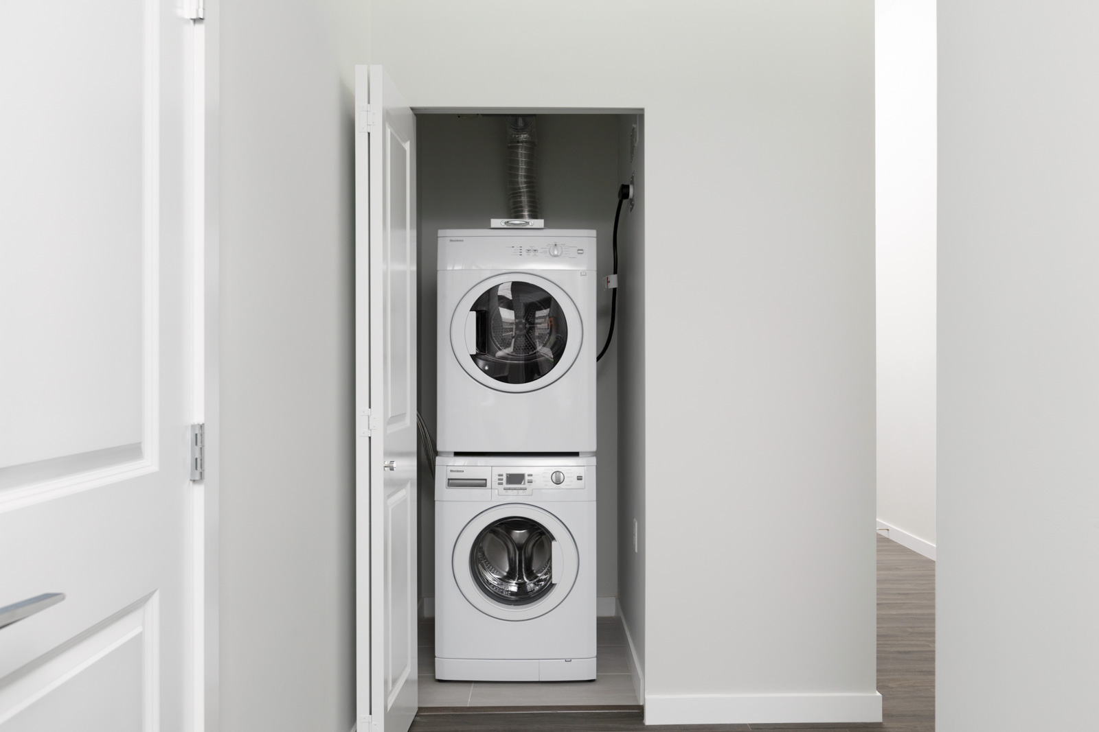 white stacked washer dryer unit with open door along wall