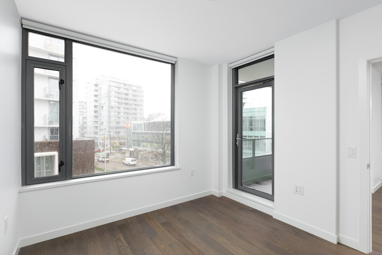 living room with hardwood floors and window looking outside in olympic village vancouver condo rental managed by birds nest properties