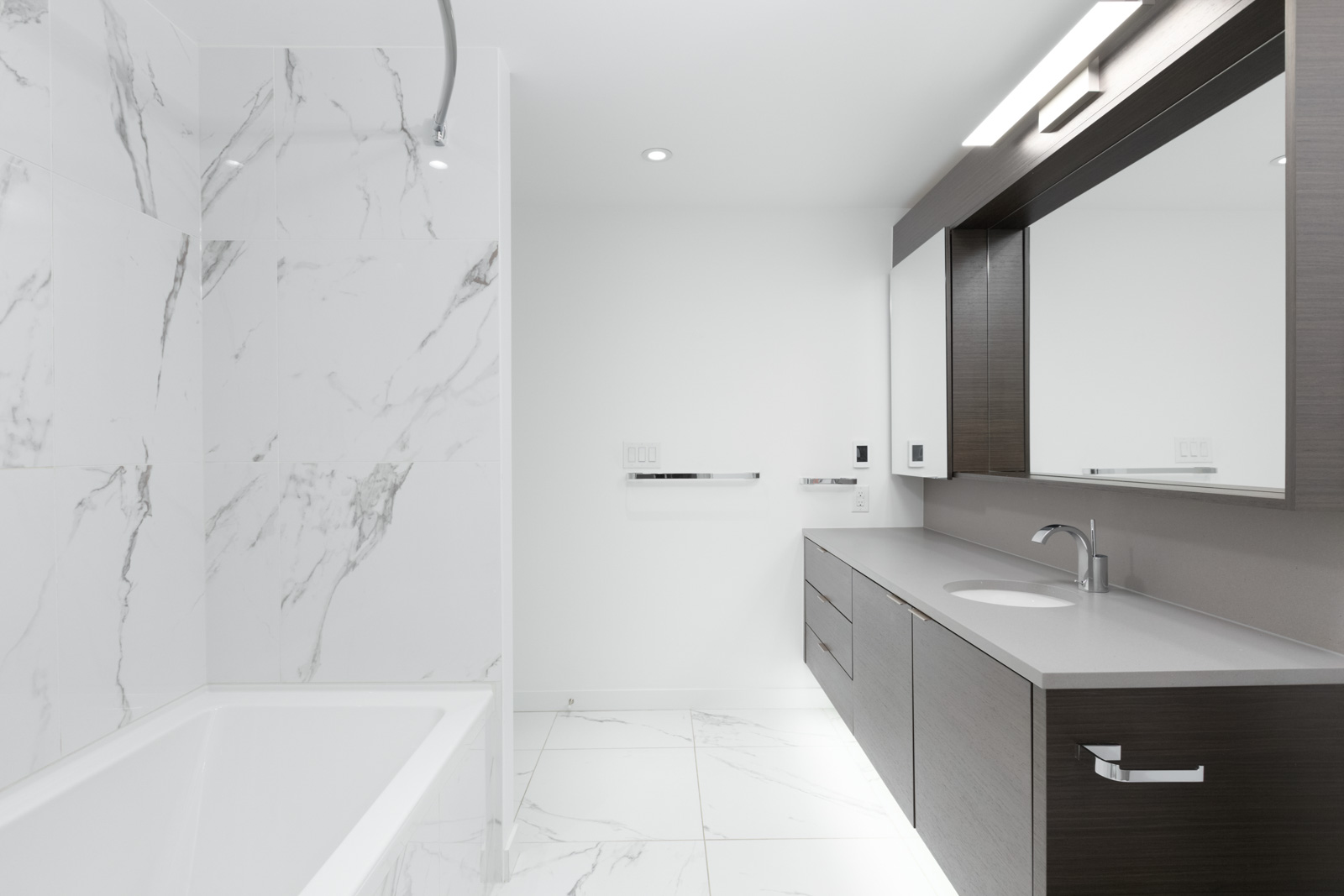bathroom with bathtub on left and counter and mirror on right and white tiling and floors