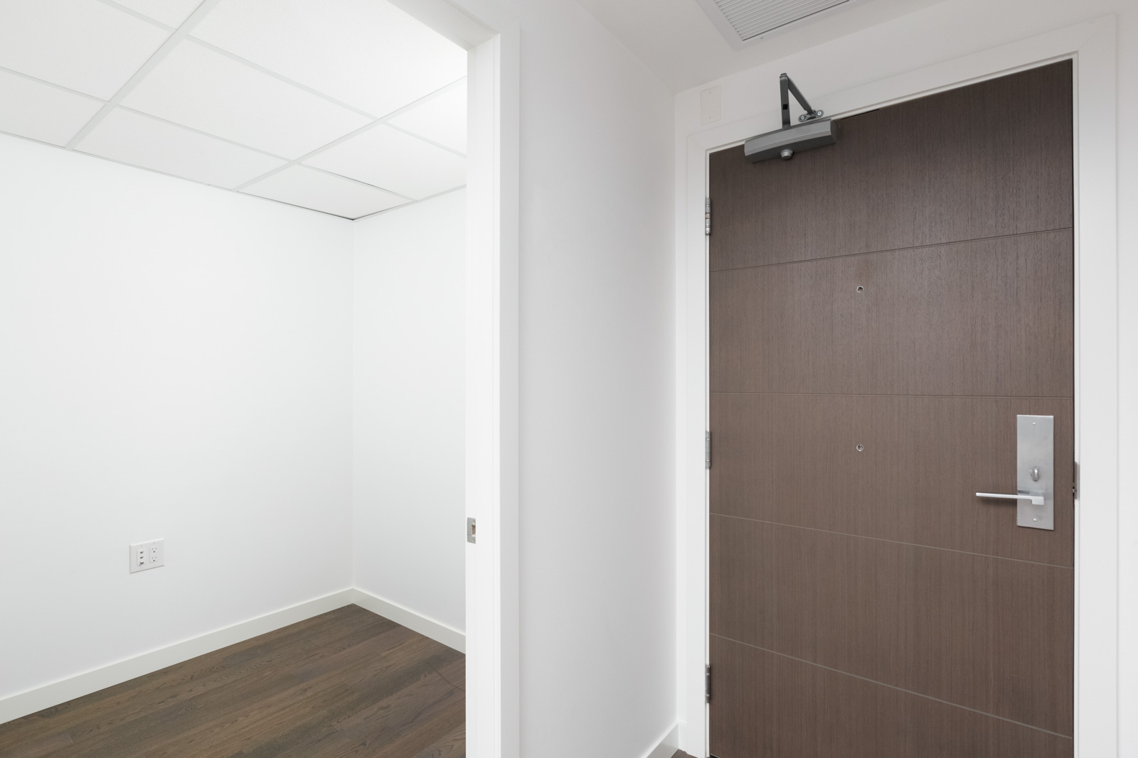 storage room on left and dark wood entrance door on right from inside a modern condo with white walls