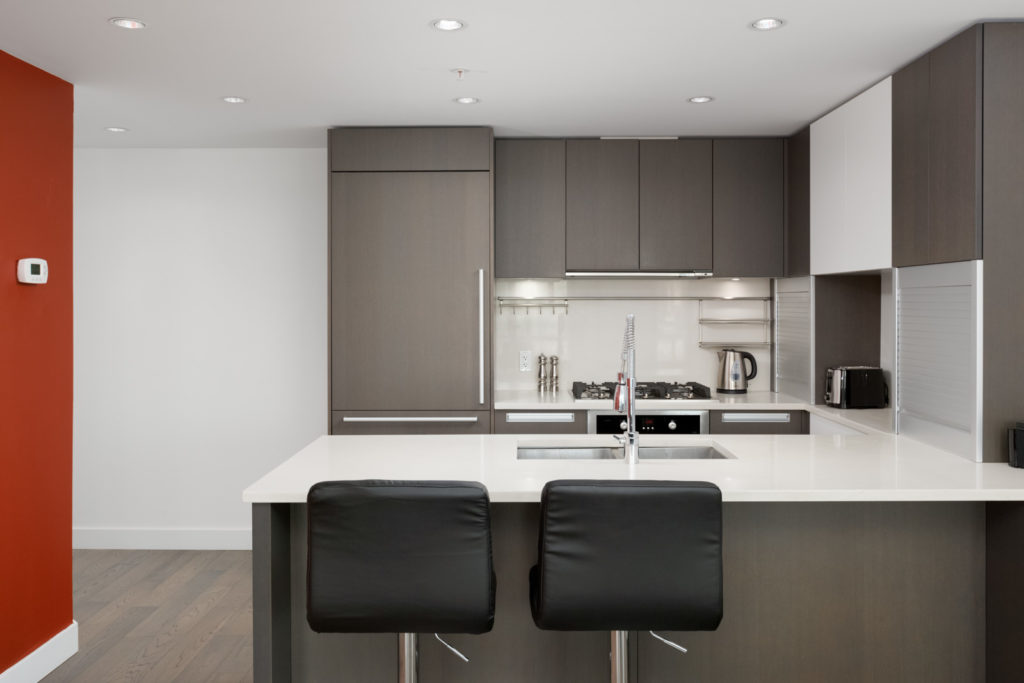 kitchen with counter and two stools with backs in false creek condo managed by birds nest properties