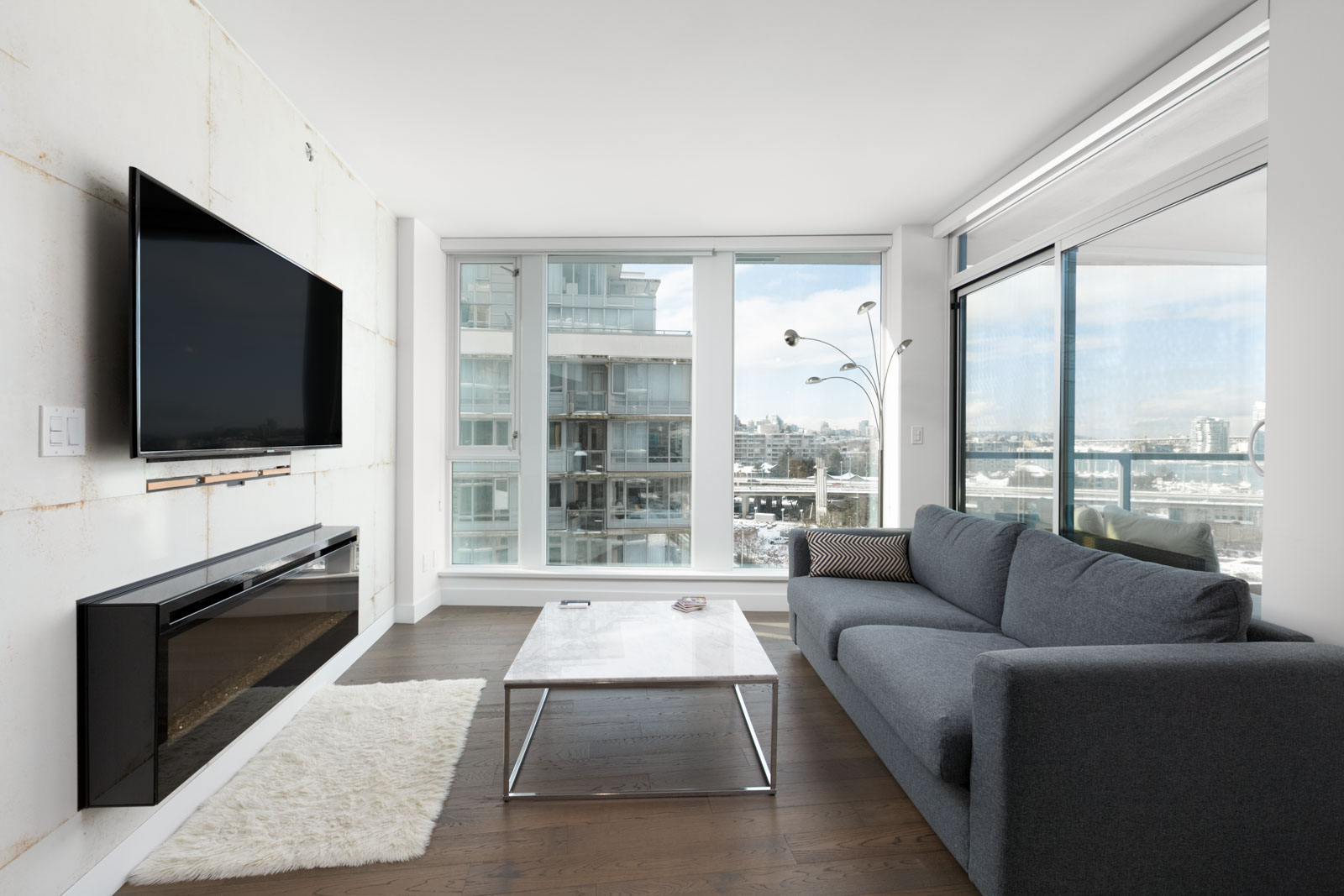 condo living room with floor to ceiling windows with flat screen tv on left wall and sofa on right and coffee table in centre with hardwood floors