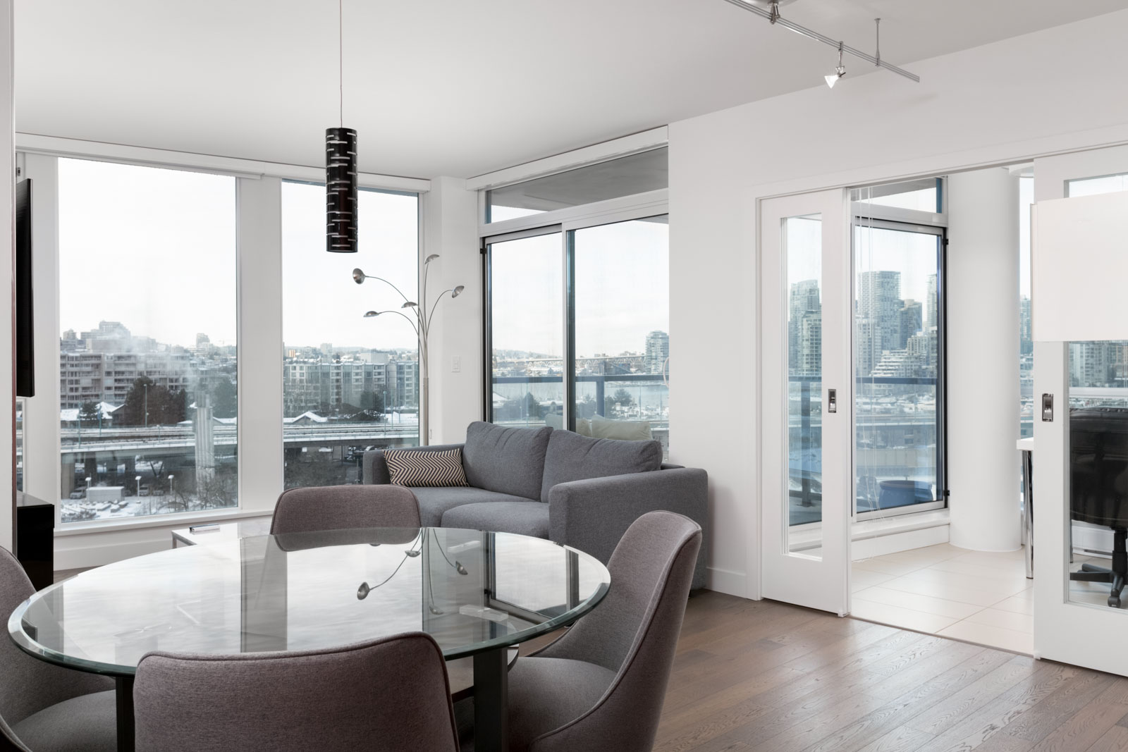 glass dining table in condo living room with floor to ceiling windows in the background with white walls