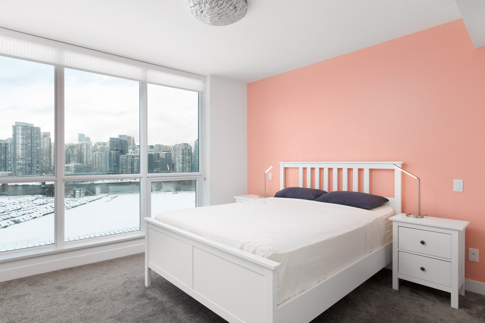 white bed with white bedding and beige wall on the right and floor to ceiling windows on the left