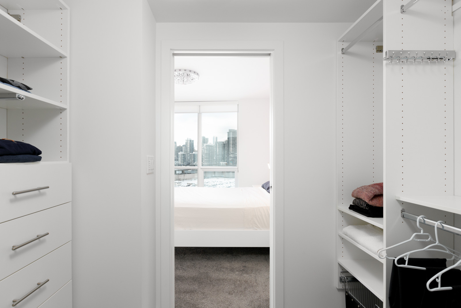 view fro walk in closet of bedroom with white walls and dark hardwood floors in condo building