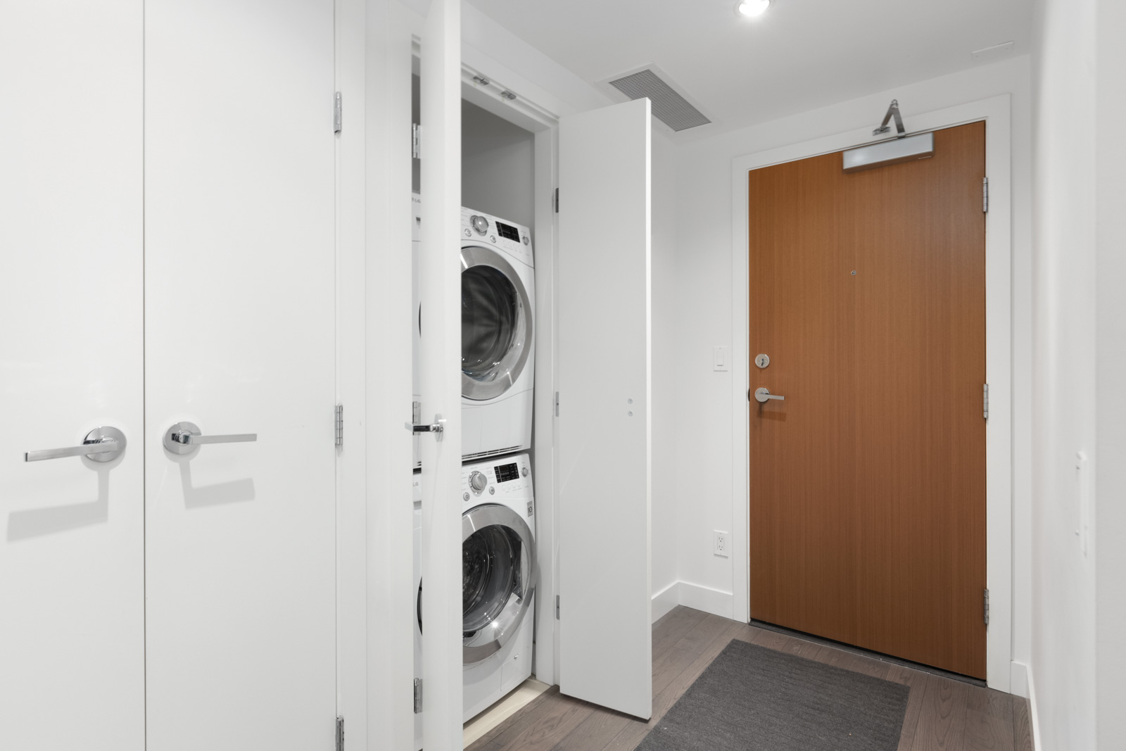 partial view of stacked white washer and dryer with white door on the left and darker wood entrance door to condo unit on the right