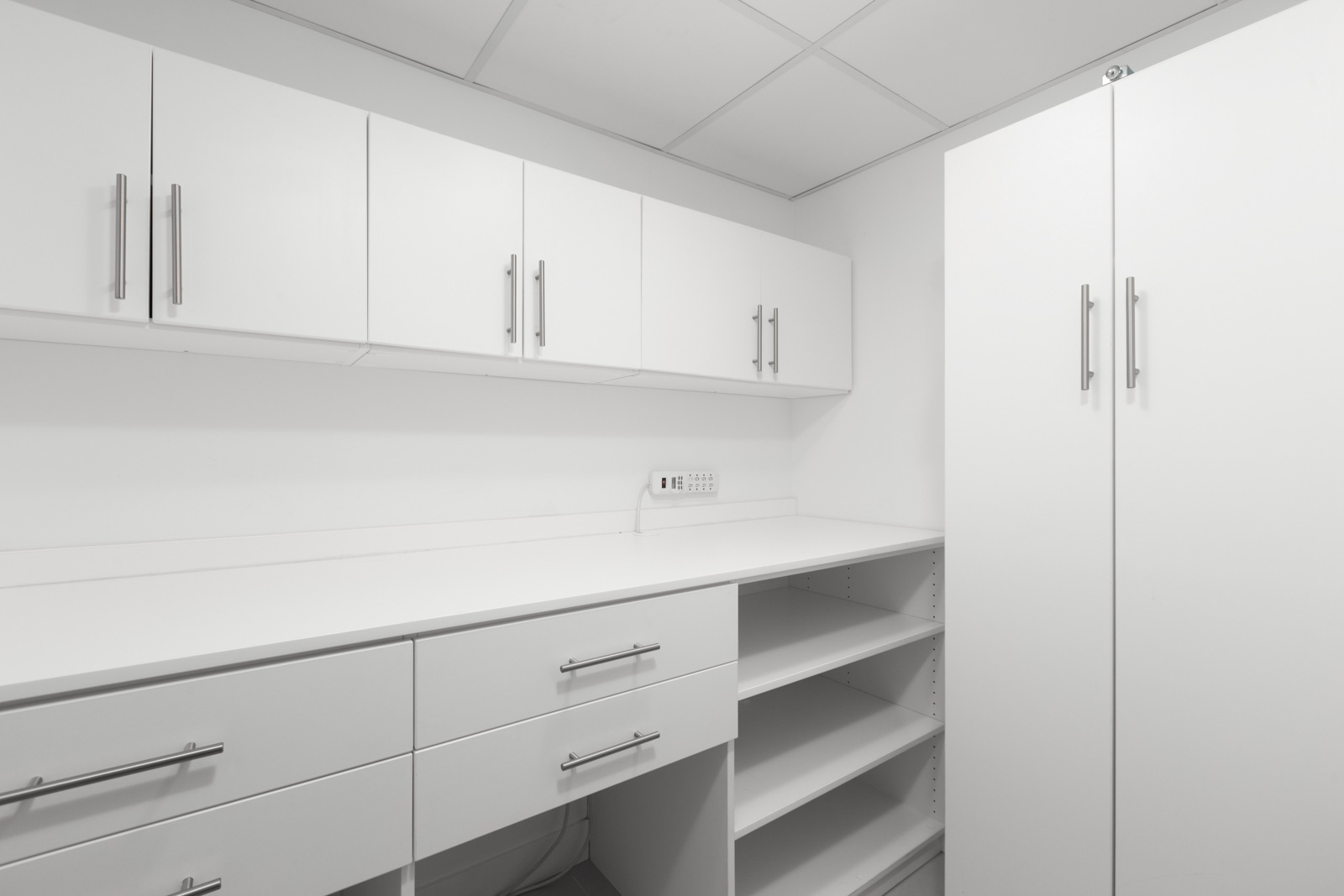 room with white cabinets and shelving and silver handles